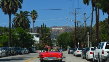 car moving to los angeles with hollywood sign in the back