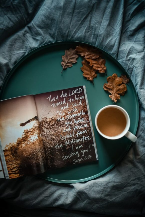 A book and a cup of tea on a tray on the bed