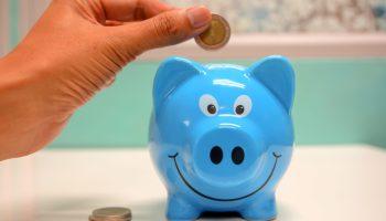 a man putting a coin in his piggybank