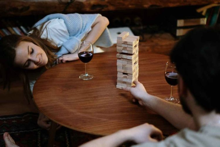 Two friends playing jenga while having a glass of wine