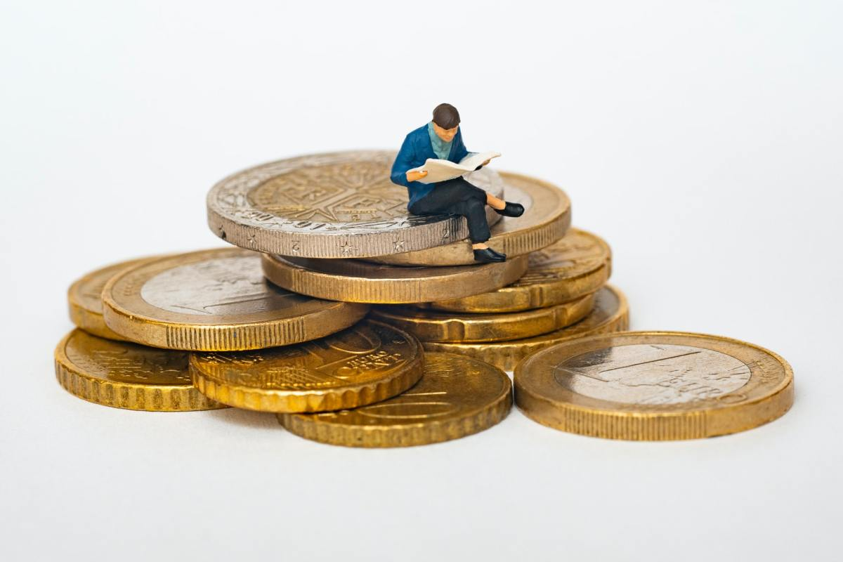 A man reading as sitting on top of a mountain of gold coins