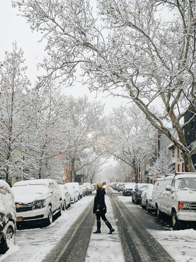 A woman wearing NYC winter essentials and standing in the middle of the street in New York