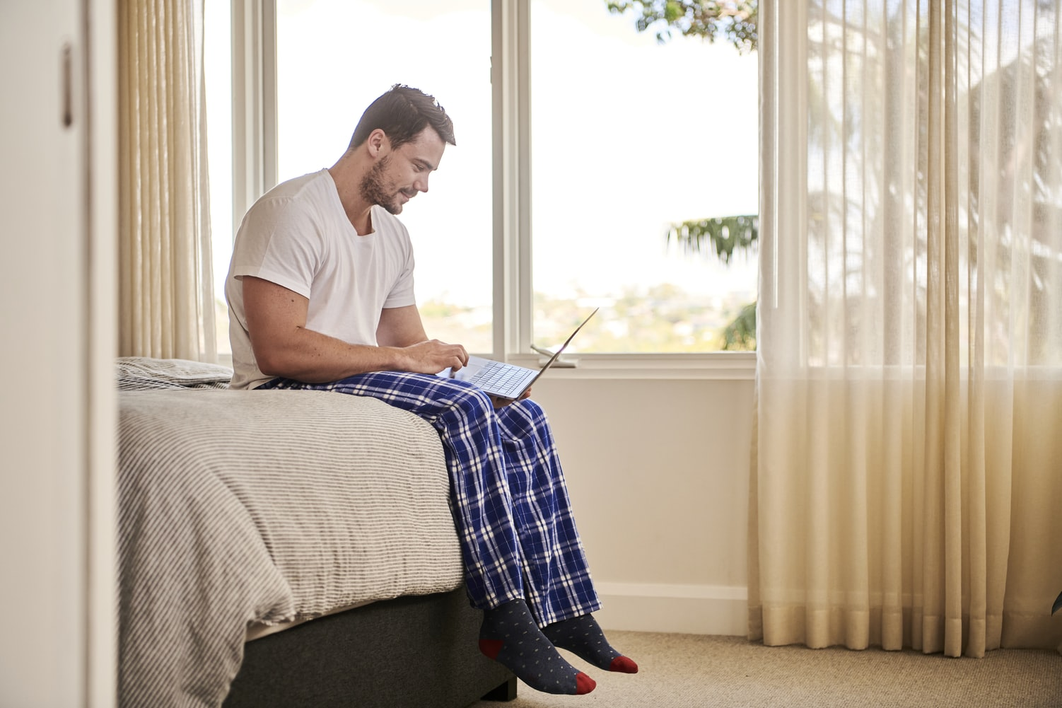 A man wearing pajamas and sitting on the bed, looking for stay at home jobs on his laptop