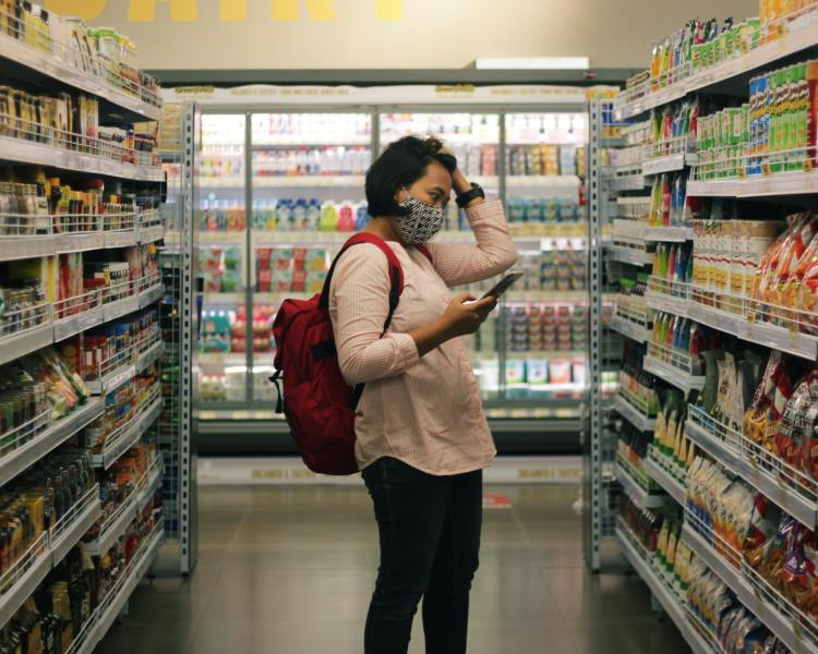 A woman confused about while looking at her grocery list in a grocery shop