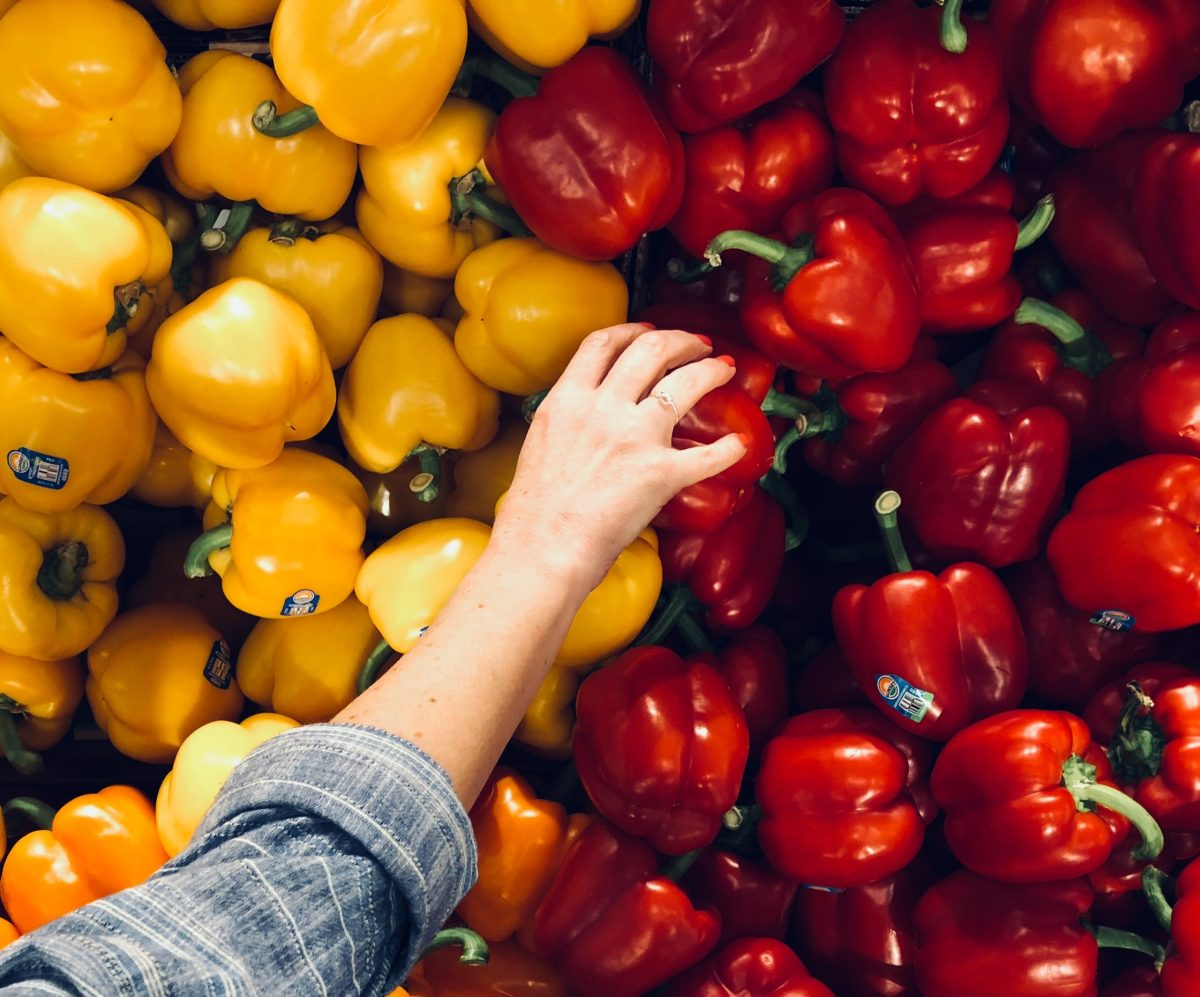 A woman picking pepper in a grocery store
