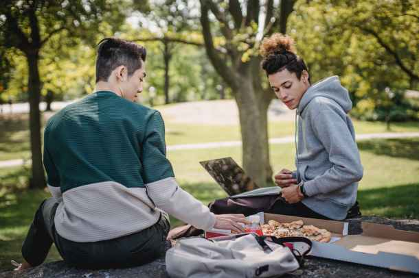 two students sitting in a park eating pizza
