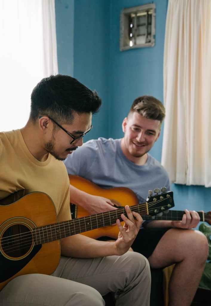 2 men holding a guitar each
