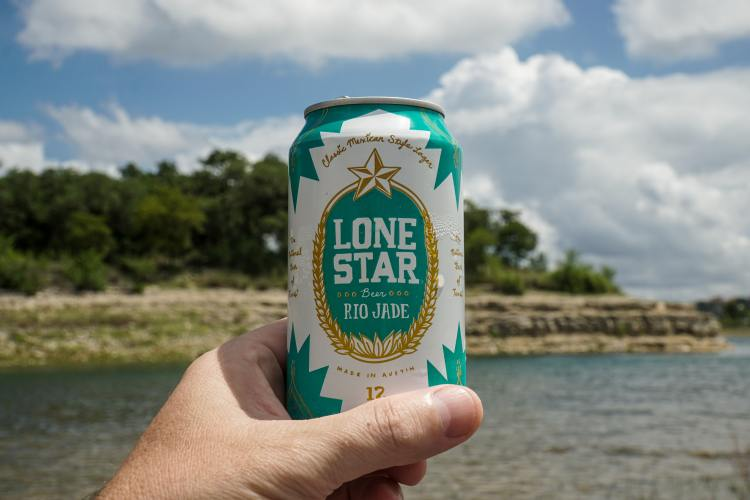 Lone Star can in a person's hand with lake in background