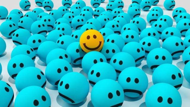 An image with many blue balls with a sad smiley face, and one yellow ball with a happy smiley face, to go with the post about emotions in writing.