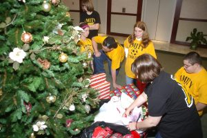 Picture of students and teachers around a Christmas tree.