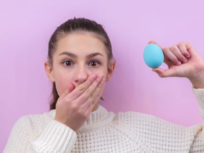 woman in white sweater holding blue balloon