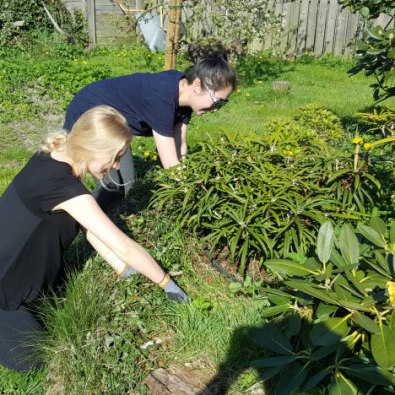 Ellen og Becca deltager i havearbejdet