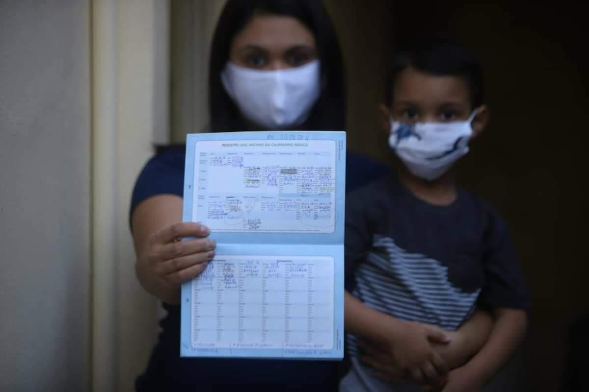 mãe e filho com carteira de vacinação