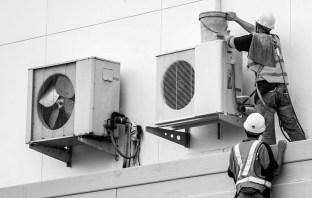 Técnicos fazendo manutenção de ar-condicionado