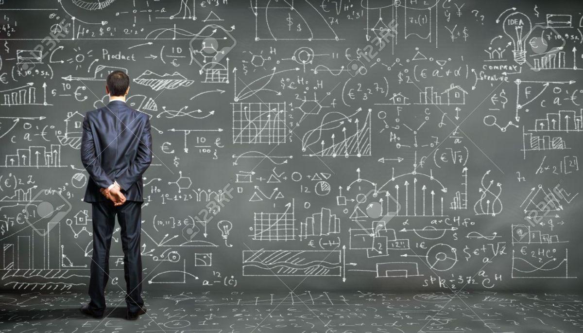 15597956-Homme-d-affaires-debout-contre-le-tableau-noir-avec-une-grande-quantit-de-donn-es-crite-sur-elle-Banque-d'images