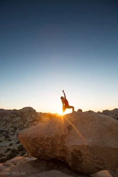 Woman doing yoga on big granite rock at Joshua Tree National Park at sunset.