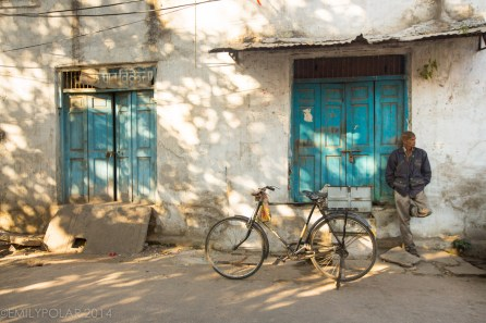 Man chilling on the street in Udaipur next to a cool bicycle.