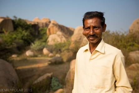 Indian man selling cake in the bouldering lands of Hampi.