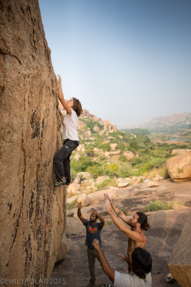 Woman climbing Boulder on the plateau in Hampi, India.
