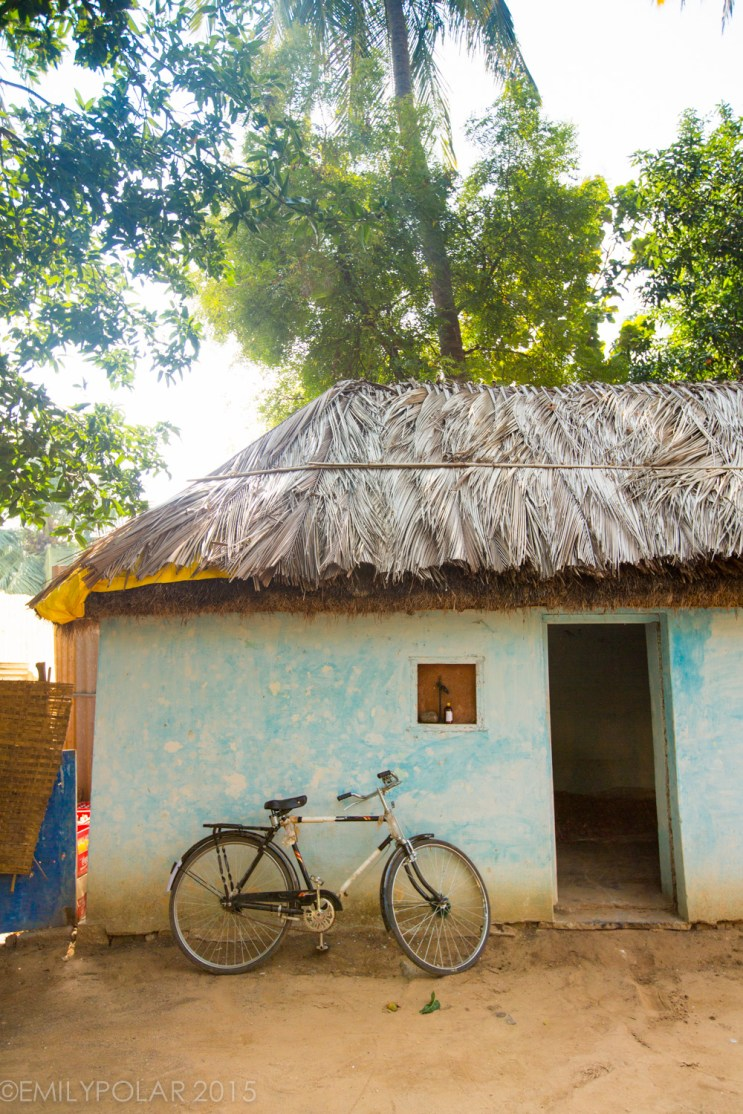 Bicycle resting up against blue mud house with straw roof in Hampi, India.