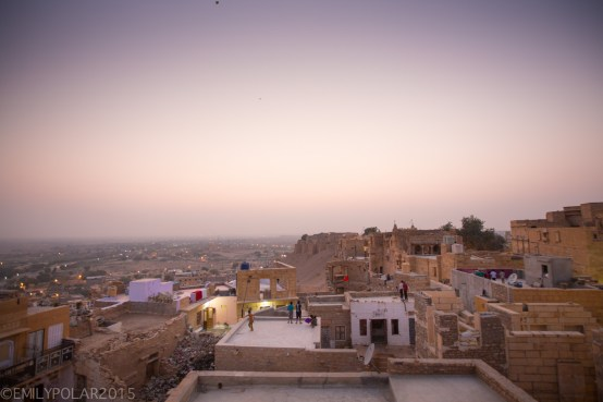 Kids play with kites flying them from the rooftops at dusk in Jaisalmer, India.