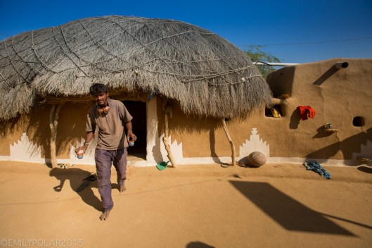 Rajasthani man walking out of his mud home to serve tea to his guests in a small village of the Thar desert.