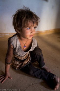 Young girl sitting on the dirt floor of her home in a small village in the Thar desert, India.