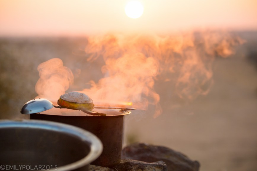 Steam rising from cooking pots at camp in the desert.