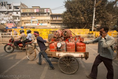 Busy streets of Old Delhi with rickshaws, bicycles and men pushing tricycle cart with propane.