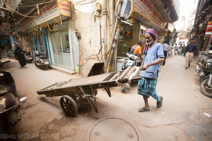 Old Indian man pushing a big wooden cart down a narrow alley in Chawri Bazar, Old Delhi.