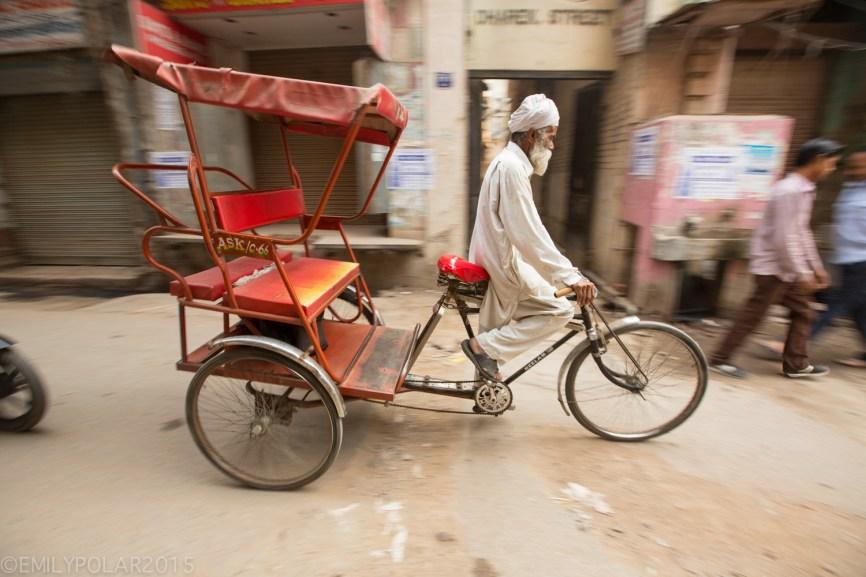 Elderly Punjabi man driving red rickshaw in the streets of Amritsar.