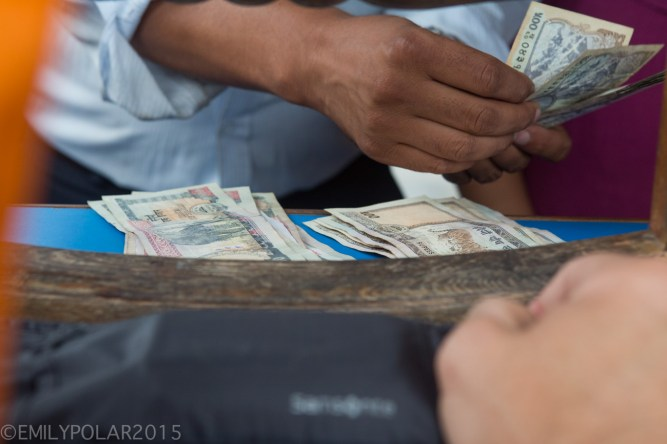 Money changer counting Nepalese Rupee for Westerner in Pokhara, Nepal.