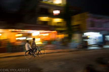Two Nepali men cruzing on a bicycle at night in the streets of Pokhara, Nepal.