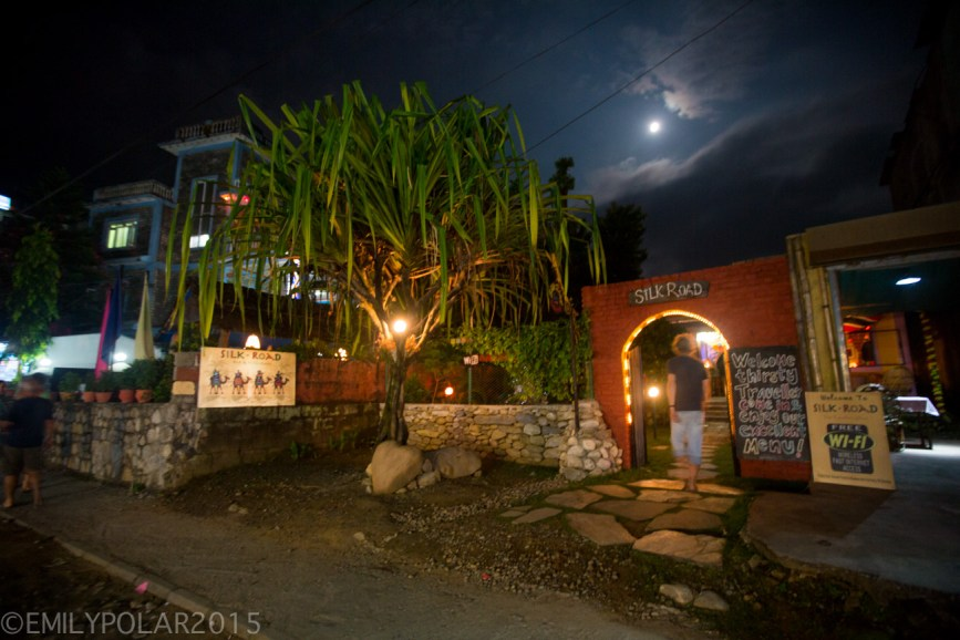 Man walking into the Silk Road restaurant at night under a full moon in the streets of Pokhara, Nepal.