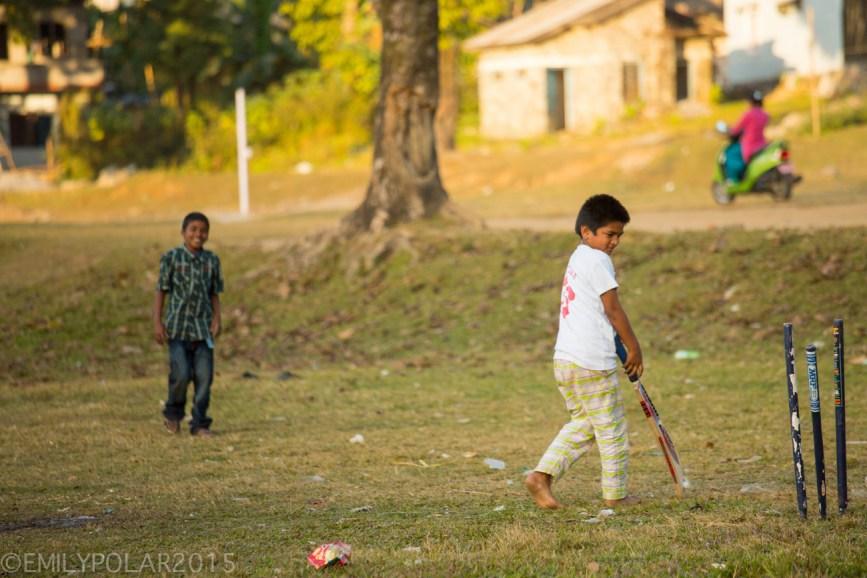 Young Nepali boys playing cricket near Pokhara lake, Nepal.