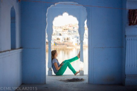 Young woman sits and enjoys the view of the Ghats under blue archway at Pushkar Lake in Rajasthan, India.