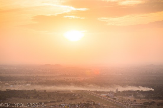 Golden sunset over Pushkar desert where trails of dust and smoke stream out from the land.
