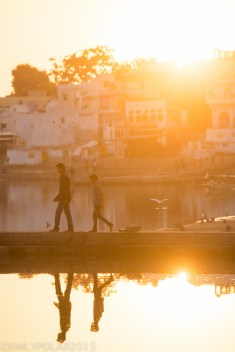 Indian boys walk along a cement pathway along Pushkar lake in the glowing light of sunset.