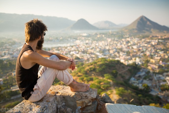 Western man enjoying the view of the town of Pushkar at sunrise from the Gayatri Temple.