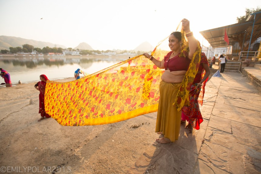 Indian women drying colorful sari fabric in the golden sunlight next to Pushkar lake.
