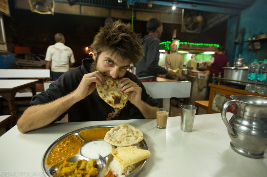 Western man eating roti with his Thali at a restaurant in Rishikesh, India.