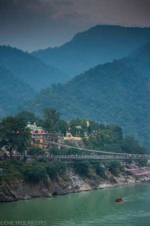 Red rafts floating down the Ganges past Laxman Jhula in Rishikesh, India.