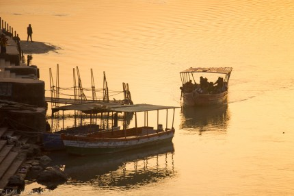 Golden sunset light shines on a shuttle boat on the Ganges river in Ram Jhula, Rishikesh.