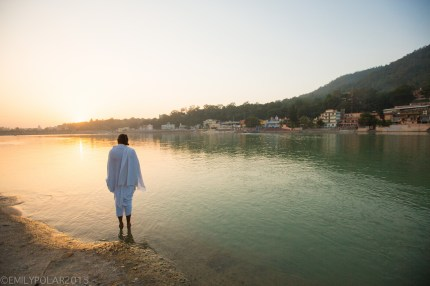 Indian man dressed in white stands in the holy Ganges river at sunset.