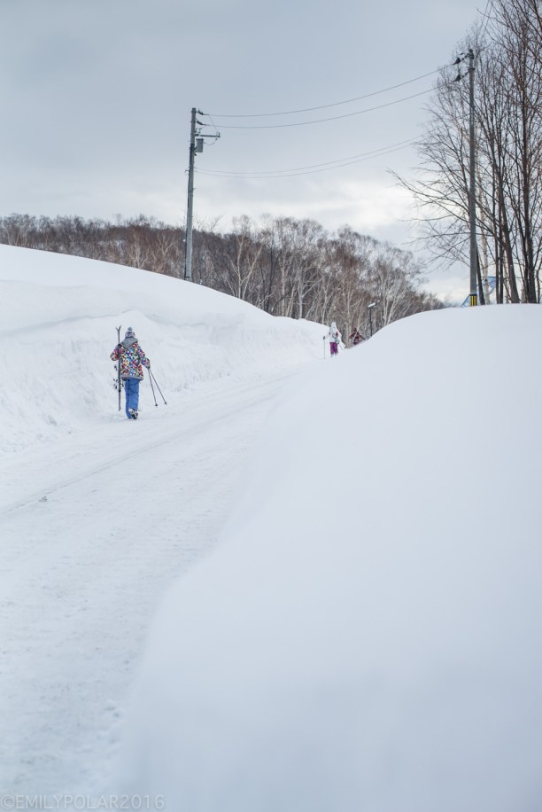 Skiers walking down snowy road near the base of Annupuri in Niseko, Japan.