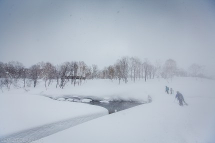 Snowboarders walking their way out of the snow drifts of Chise backcountry near the Chise Onsen in Niseko, Japan.