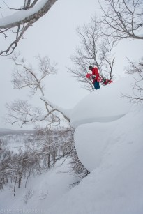 Snowboarder standing on top of huge snow pillow at Chisenupuri in Niseko, Japan.