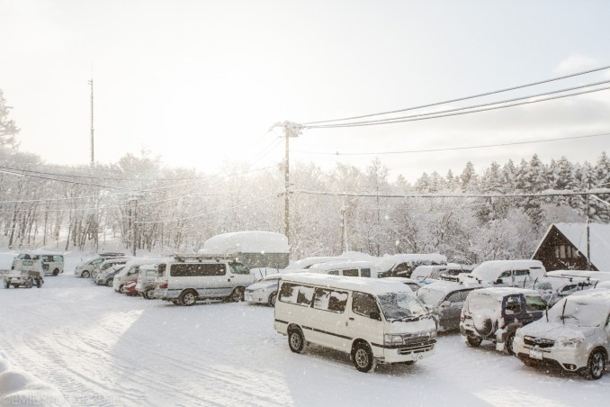 Snow falling in the morning light over the parking lot at Moiwa in NIseko, Japan.