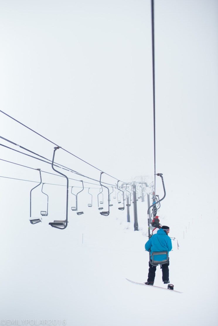 Snowboarder in a blue jacket riding a one seater chair lift in a white out to the top of Hirafu, Resort.