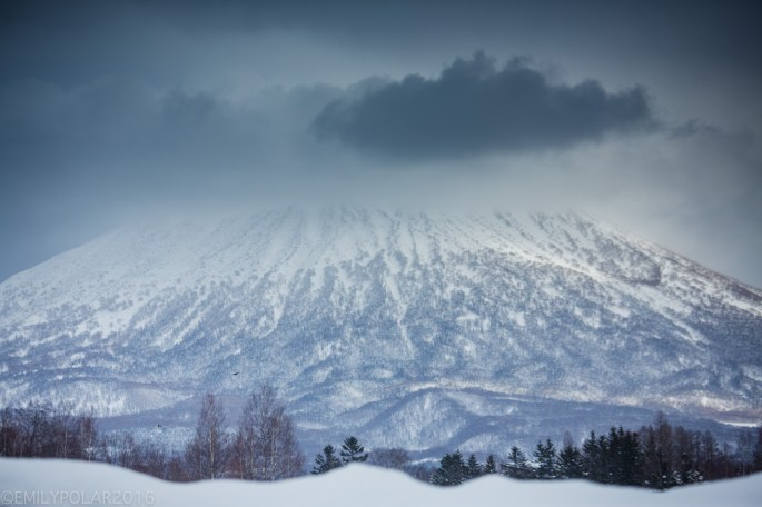 Clouds hug to the snowy peak of Mt. Yotei in the cool winter landscape of Niseko, Japan.